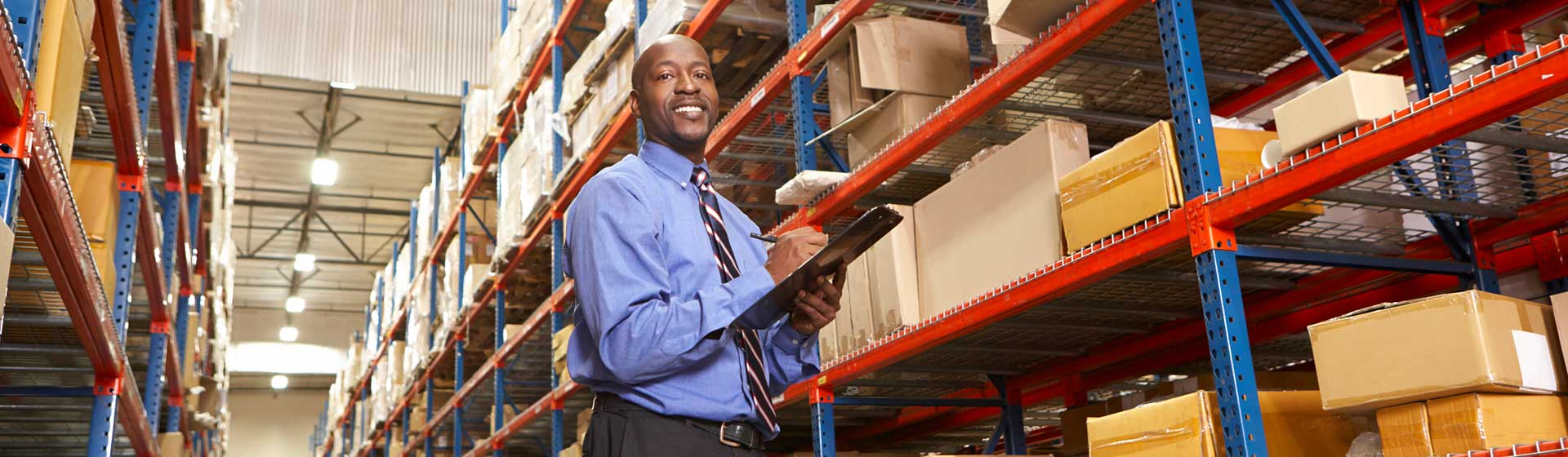 Smiling man in warehouse writing on clipboard