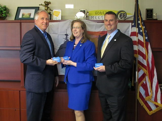 Three bank members stand alongside American flag