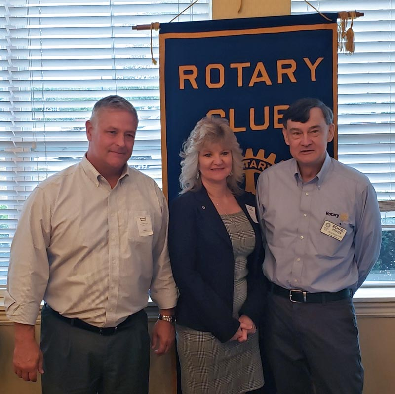 Two men and one woman standing in front of Rotary Club banner