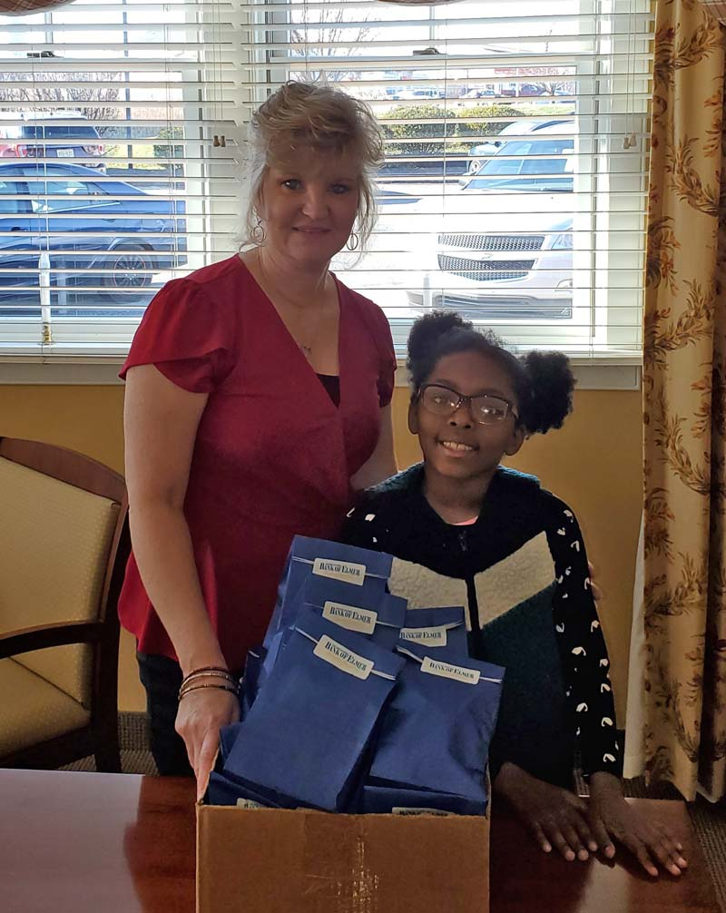 Young girl with bank employee displaying Elmer Bank goodie bags.