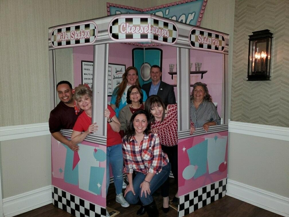 Group of employees posing inside a diner mockup