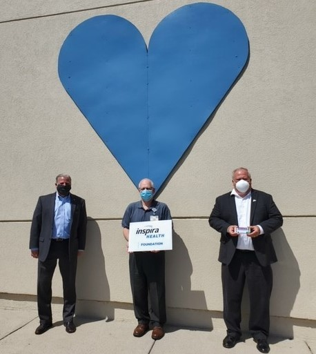 Three men in suits standing against wall with giant blue heart on wall
